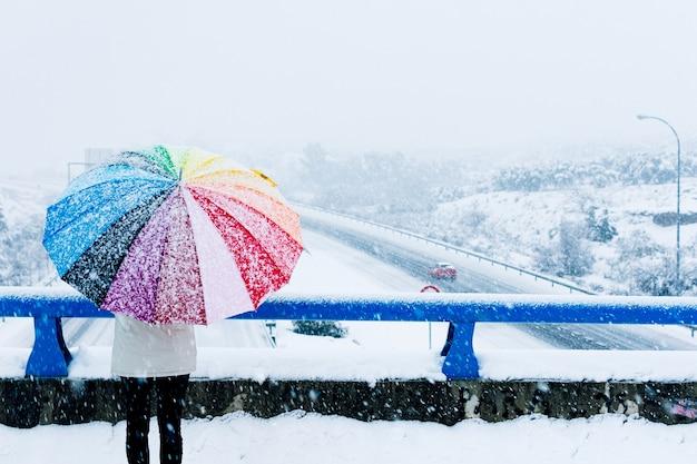 Vue arrière d'une femme avec parapluie coloré face à une autoroute enneigée