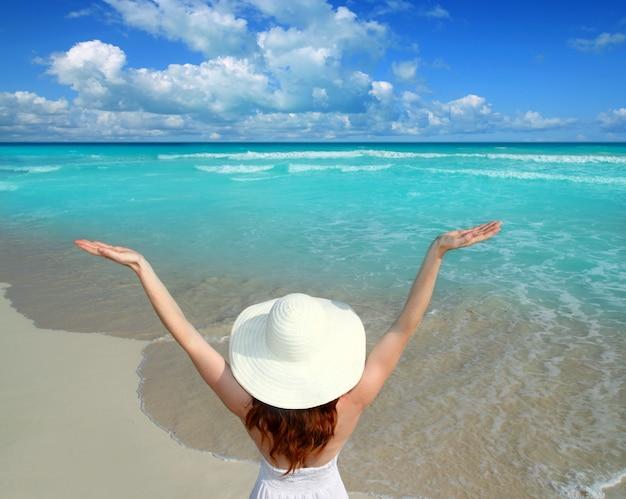 Vue arrière, femme, plage, chapeau, bras ouverts