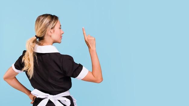 Vue arrière, de, femme, pointant haut, debout, contre, arrière-plan bleu