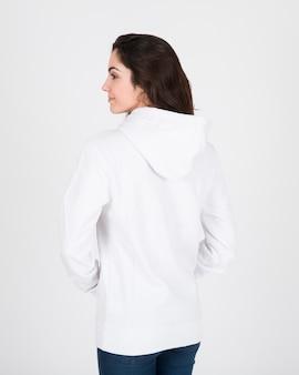 Vue arrière de la femme portant un chandail à capuchon blanc