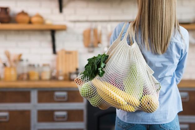 Vue arrière femme portant un sac réutilisable avec des fruits biologiques