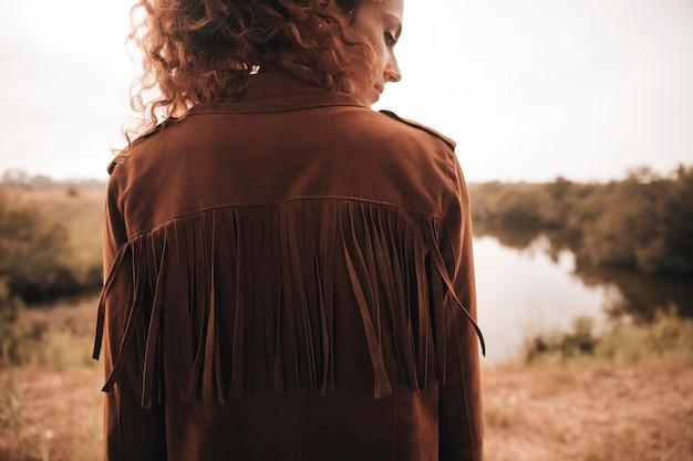 Vue arrière femme posant à côté d'un étang