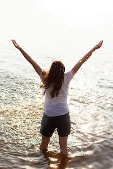Vue arrière de la femme posant dans l'eau au lac