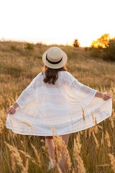 Vue arrière de la femme posant à l'extérieur dans les champs