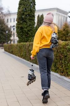 Vue arrière d'une femme posant tout en tenant des patins à roues alignées