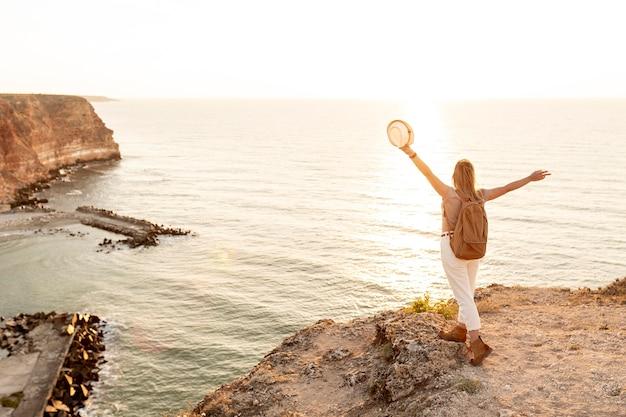 Vue arrière femme profitant du coucher de soleil sur une côte