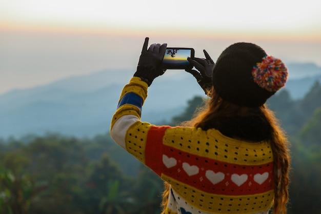 Vue arrière d'une femme en pull et chapeau épais tenant un smartphone prenant une photo de la vue sur la montagne au lever du soleil du matin.