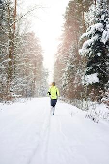 Vue arrière de la femme qui court dans la forêt d'hiver