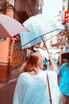 Vue arrière d'une femme qui marche avec un parapluie transparent dans la ville des pluies