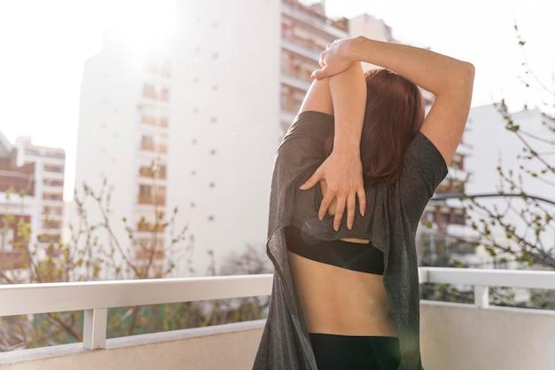 Vue arrière femme qui s'étend sur balcon