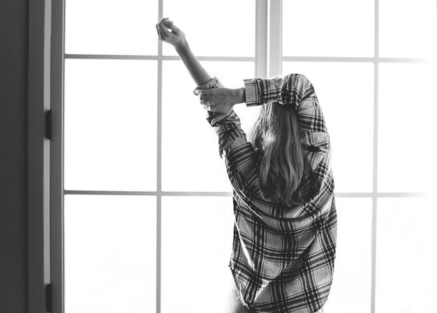 Vue arrière de la femme qui s'étend les bras le matin