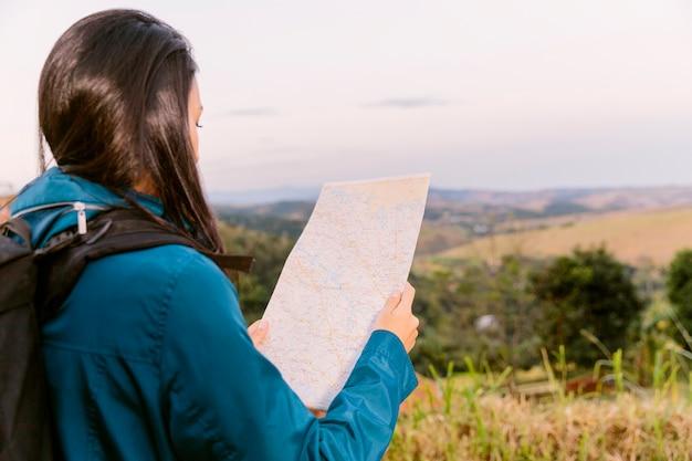 Vue arrière d'une femme à la recherche sur la carte
