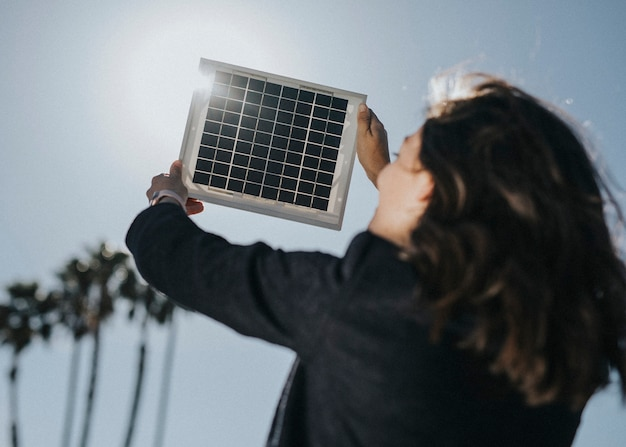 Vue arrière d'une femme respectueuse de l'environnement tenant un panneau solaire dans le ciel