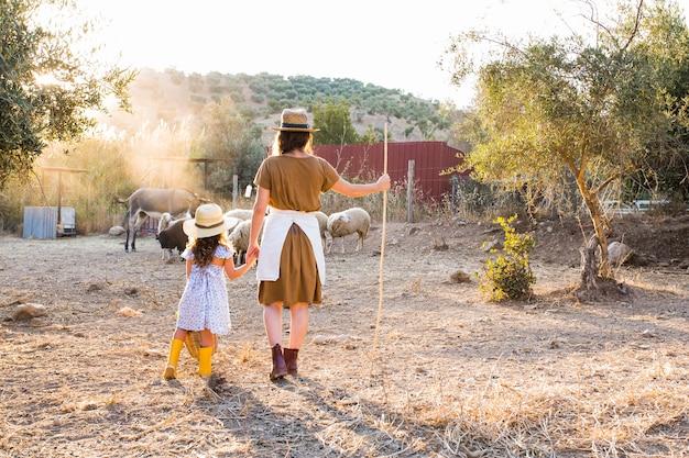 Vue arrière de la femme avec sa fille à la recherche d'animaux dans le champ