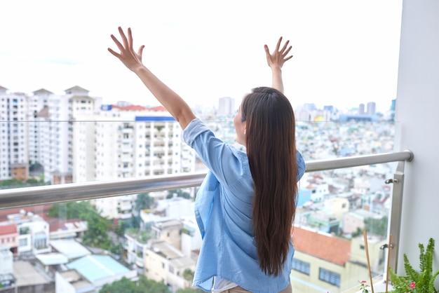 Vue arrière d'une femme sportive active qui s'étend sur un balcon