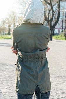 Vue de l'arrière d'une femme sportive dans une cagoule se préparant à courir dans le parc le matin