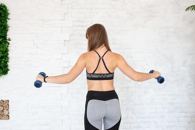 Vue arrière d'une femme sportive avec des haltères. vue arrière de la femme sportive