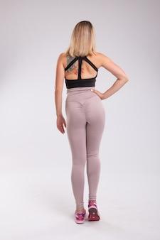 Vue arrière de la femme sportive. vue arrière de la femme sportive assise portant des leggings.