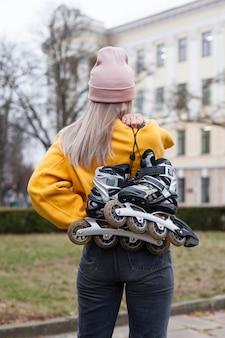 Vue arrière d'une femme tenant des patins à roues alignées