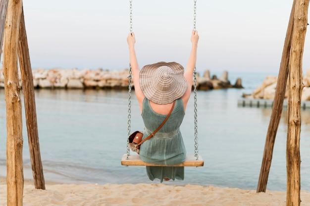 Vue arrière de la femme de tourisme senior dans la balançoire de plage