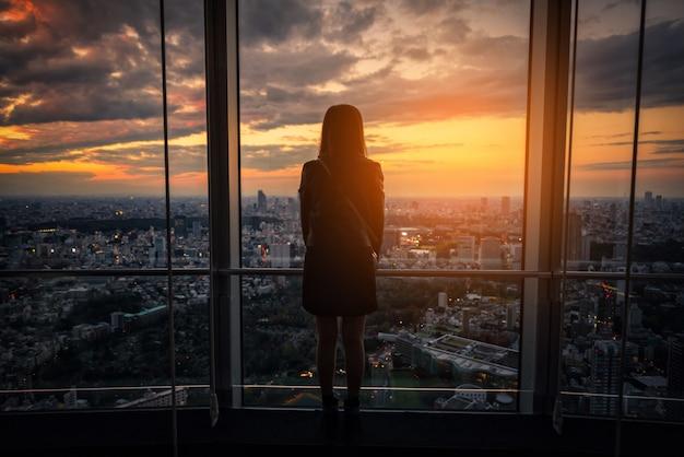 Vue arrière de la femme de voyageur à la recherche de tokyo skyline sur la terrasse d'observation au coucher du soleil