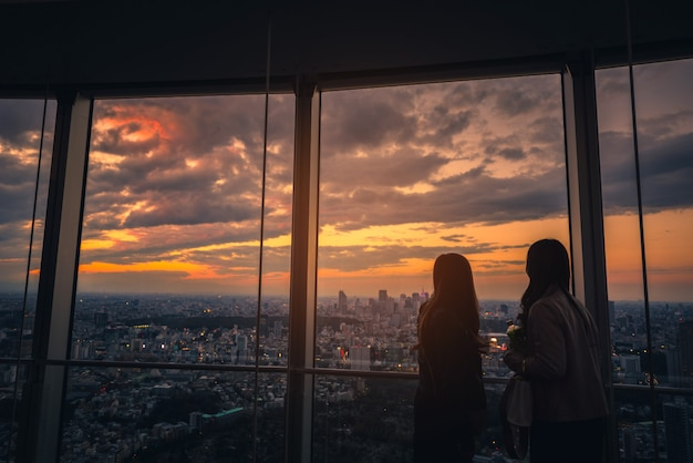 Vue arrière de la femme de voyageur à la recherche de tokyo skyline et vue de gratte-ciels sur la terrasse d'observation au coucher du soleil au japon.
