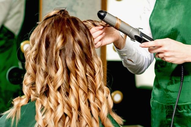 Vue arrière des femmes coiffeurs mains curling cheveux femmes avec fer à friser dans un salon de coiffure