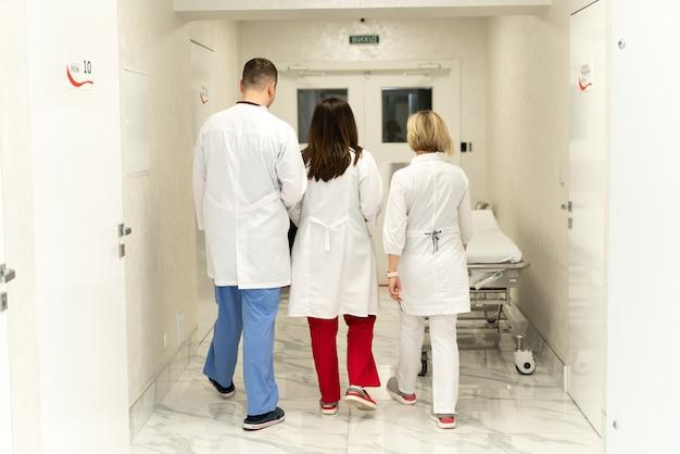 Vue arrière des femmes et des hommes, médecins. médecins marchant dans le hall. les travailleurs de la santé, les médecins et les infirmières au travail à l'hôpital. concept d'équipe de la clinique
