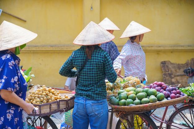 Vue arrière des femmes, vendeur de rue féminin en fruits, marché aux fleurs sur le vélo