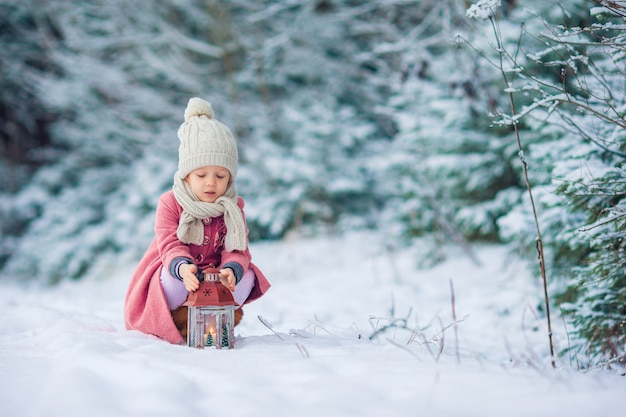 Vue arrière d'une fille adorable avec lampe de poche en plein air d'hiver