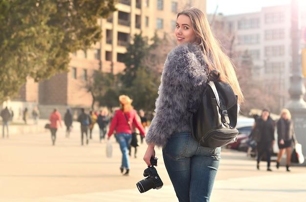 Vue arrière d'une fille avec un appareil photo numérique sur une rue bondée ba