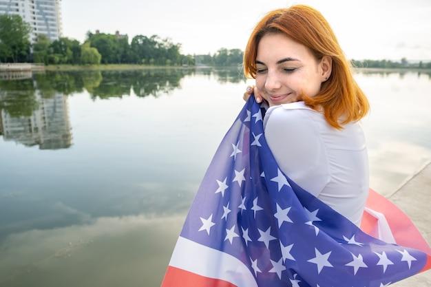 Vue arrière d'une fille aux cheveux rouges heureuse avec le drapeau américain sur ses épaules. jeune femme positive célébrant la fête de l'indépendance des états-unis.