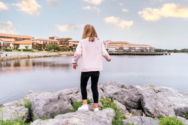 Vue arrière d'une fille blonde caucasienne marchant parmi les pierres dans un lac du village