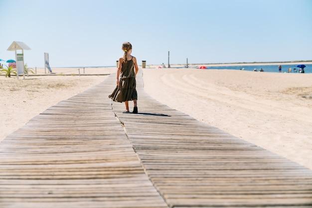 Vue arrière fille blonde avec masque facial en vacances à travers un chemin dans le sable d'une plage avec une robe verte au milieu d'une pandémie de coronavirus