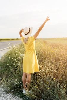 Vue arrière fille avec chapeau profitant de la nature