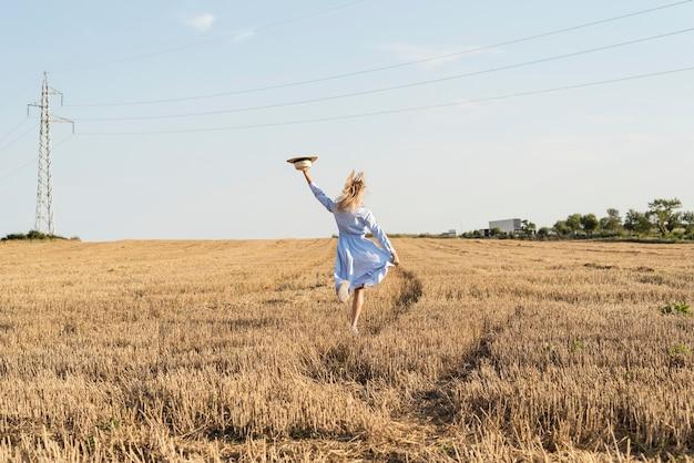 Vue arrière fille en cours d'exécution dans un champ