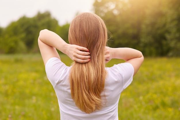 Vue arrière d'une fille élancée méconnaissable bénéficiant d'un beau paysage