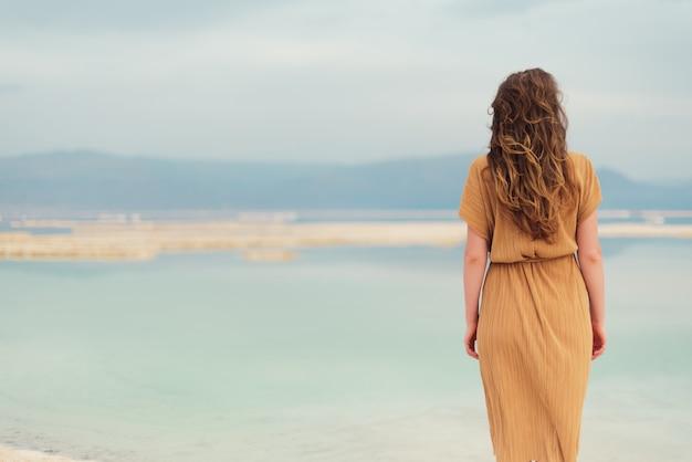 Vue arrière d'une fille élégante vêtue d'une robe au bord de la mer
