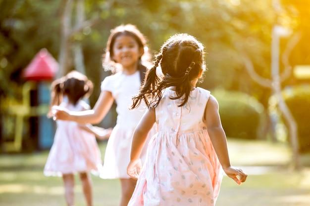 Vue arrière de la fille de l'enfant asiatique en cours d'exécution à son amie et jouer ensemble dans le parc de couleur vintage