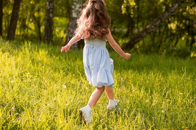 Vue arrière d'une fille qui court dans le parc