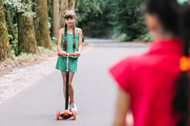 Vue arrière de la fille en regardant son amie debout sur un scooter
