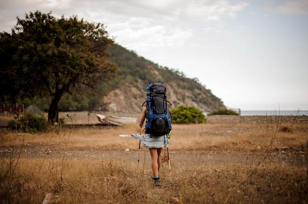 Vue arrière fille avec sac à dos et bâtons de randonnée à travers le champ