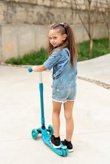 Vue arrière de la fille avec un scooter bleu