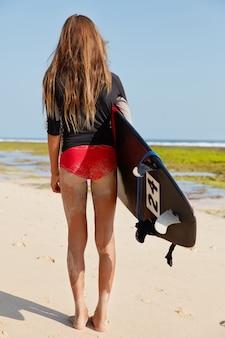 Vue arrière de la fille de surf active va surfer sur l'océan, détient une planche de surf, habillée en bikini rouge
