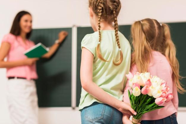 Vue arrière des filles cachant un bouquet de fleurs pour leur professeur