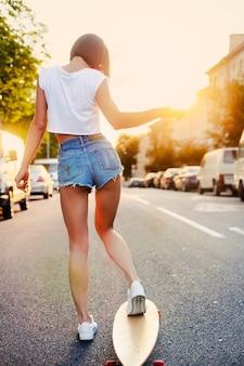 Vue arrière de la formation de l'adolescence avec planche à roulettes