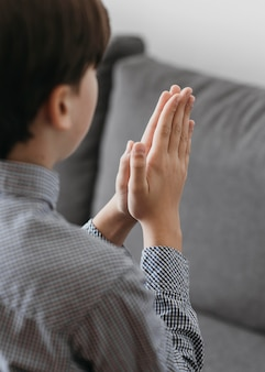 Vue arrière garçon priant sur le canapé à la maison