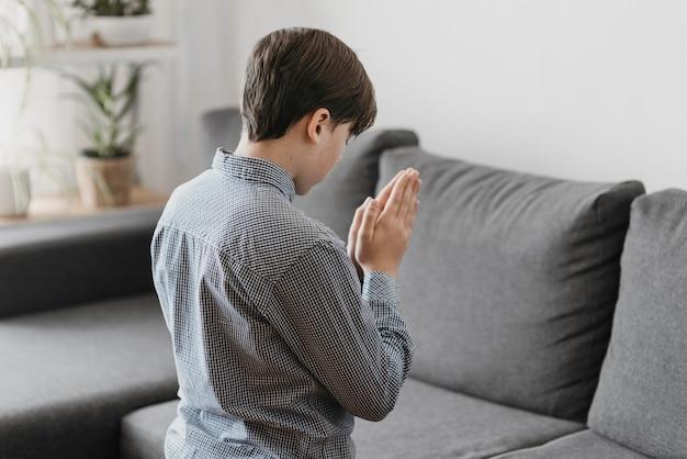 Vue arrière garçon priant dans le salon
