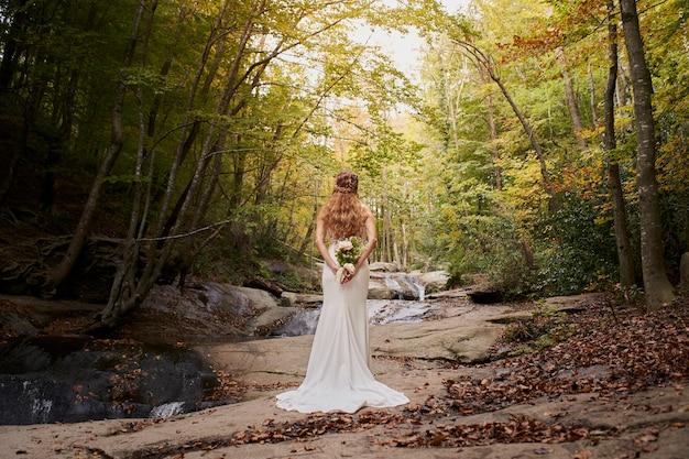 Vue arrière grand angle de la belle jeune mariée tenant un bouquet sur le dos dans la forêt