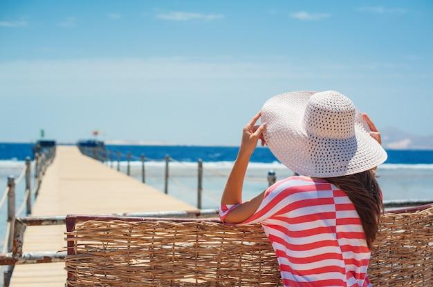 Vue arrière gros plan de la femme au chapeau blanc regardant vers l'océan bleu et le ciel.